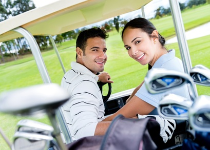 Happy couple in a cart playing golf
